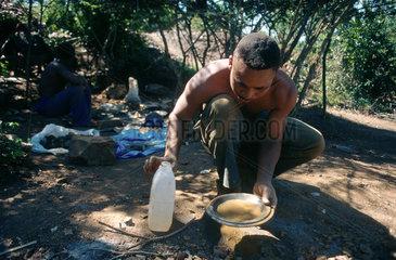Barberton  Suedafrika  ein Mann schuerft nach Gold in einem Waschteller
