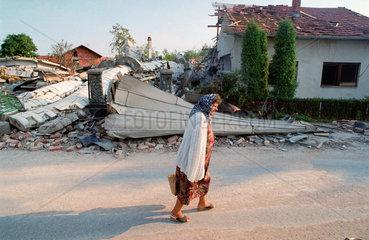 Prijedor  Bosnien-Herzegowina  eine aeltere Frau auf der Strasse  im Hintergrund Truemmer einer Moschee