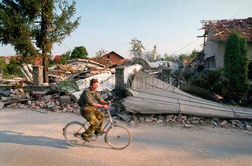 Prijedor  Bosnien-Herzegowina  ein Radfahrer auf der Strasse  im Hintergrund Truemmer einer Moschee