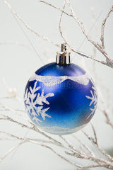 Blue bauble hanging from silver branches