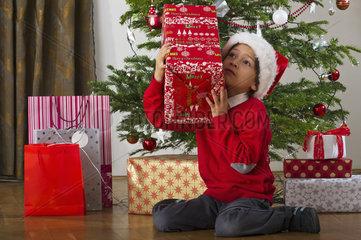 Boy sitting beside Christmas tree  shaking gift