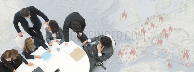 Executives in meeting  large map depicting European economic crisis in background