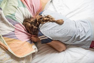 Maedchen versteckt sich im Bett