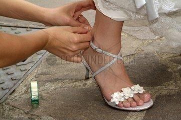 Bridesmaid adjusting bride's shoe