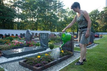 Boxberg  Deutschland  eine Frau giesst Blumen auf einem Friedhof