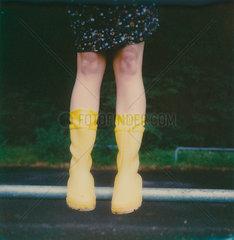 Beine einer Frau mit Gummistiefeln