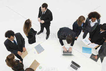 Business associates working together in small groups around table