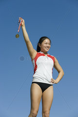 Female athlete being honored on podium  holding up medal