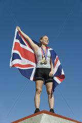 Female athlete being honored on podium  holding up British flag