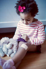 Little girl looking at adhesive bandage on knee