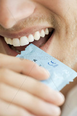 Man opening condom wrapper with his teeth  cropped