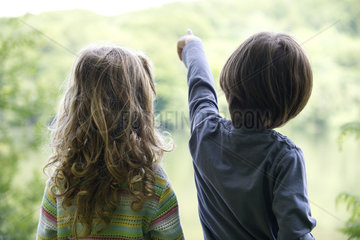 Children looking at lake as boy points