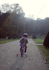 Little girl riding bicycle  rear view
