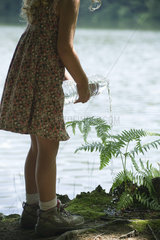 Girl watering plant with bottle of water