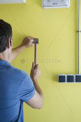 Man hammering nail into wall  rear view