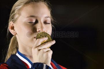 Female athlete kissing gold medal  portrait