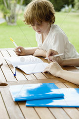 Boy coloring outdoors