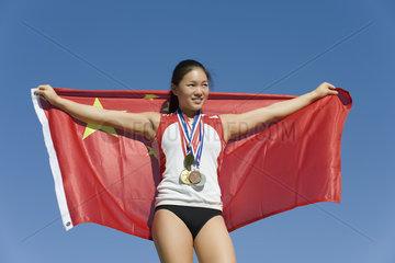 Female athlete on winner's podium  holding Chinese flag