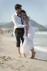 Bride and groom embracing at the beach