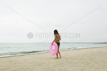 Woman standing on beach  holding inflatable ring  rear view