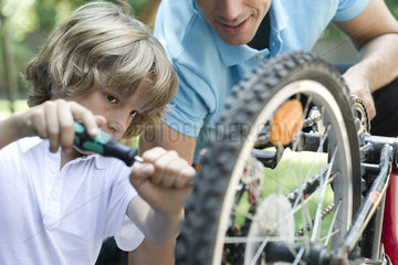 Boy repairing bicycle with father's help