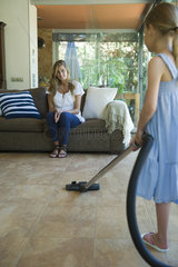 Woman sitting on sofa smiling  daughter vacuuming floor in foreground