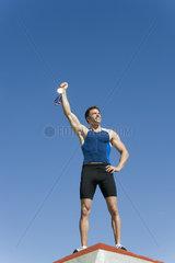 Male athlete on podium  holding up gold medal