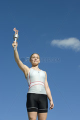 Female athlete holding up torch