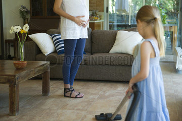 Daughter helping pregnant mother vacuum floor  cropped