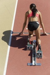 Woman crouched in starting position on running track  rear view