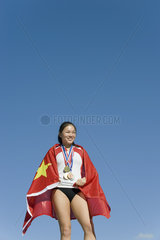 Female athlete on winner's podium  wrapped in Chinese flag