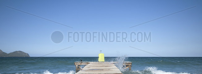 Waves crashing against dock  yellow suitcase at end of dock