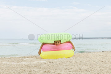 Girl playing with stack of inflatable rings on beach