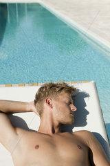 Man sunbathing beside pool