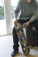 Man repairing skateboard