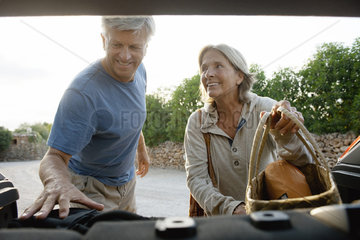 Senior couple loading bags into car