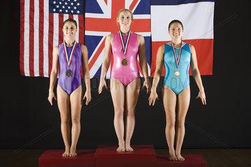 Female gymnastic medalists stanidng on winner podium  portrait
