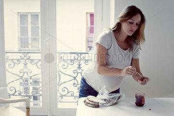 Mid-adult woman spreading jam on toast