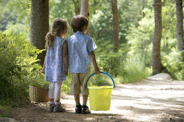 Children together on path in woods  girl carry basket and boy carrying bucket