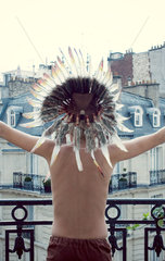 Boy in Indian headdress with arms outstretched  rear view