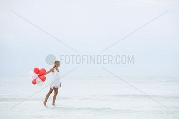 Woman walking on water  carrying bunch of balloons