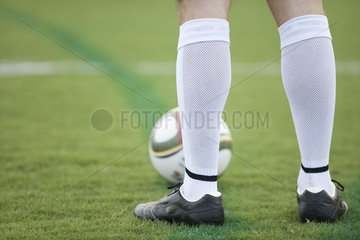 Soccer player standing on field  low section