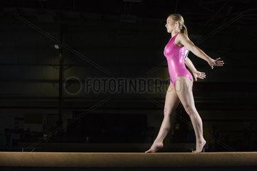 Female gymnast performing routine on balance beam