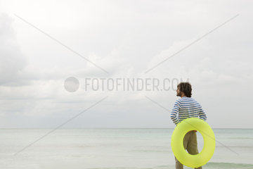 Young man with inflatable ring  looking at ocean view