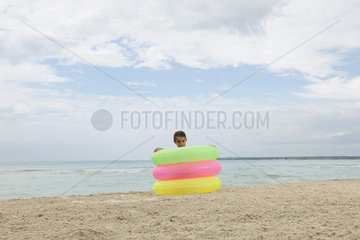 Girl playing with stack of infltable rings on beach