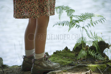 Girl standing at water's edge  low section