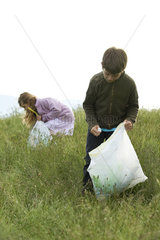 Children picking up trash in field