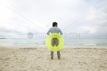 Young man staning on beach with inflatable ring  rear view