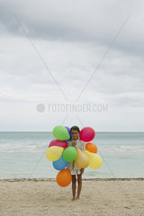 Girl with bunch of colorful balloons on beach