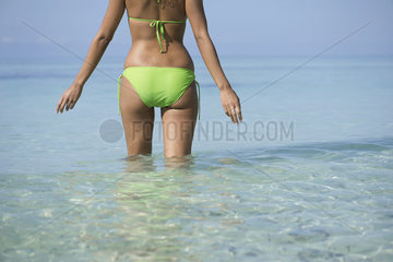 Woman in bikini standing in water  mid section
